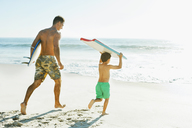Father and son carrying surfboard and bodyboard on beach - CAIF03619