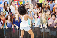 Fans watching performer sing at music festival - CAIF03625