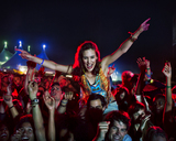 Cheering woman on manÍs shoulders at music festival - CAIF03631