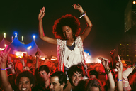 Cheering woman on manÍs shoulders at music festival - CAIF03634