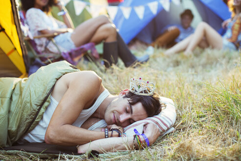 Man in tiara sleeping in sleeping bag outside tents at music festival - CAIF03646
