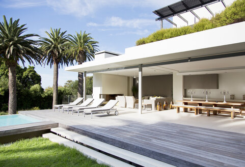 Lounge chairs on deck of modern house - CAIF03673