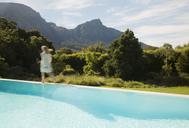 Woman walking along swimming pool - CAIF03691