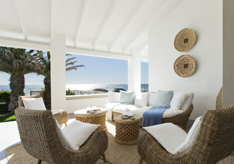 Wicker sofa and chairs on luxury patio - CAIF03697