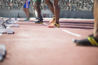 Runners standing at starting blocks on track - CAIF03730