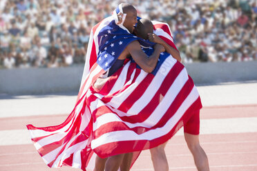 Track and field athletes wrapped in American flag on track - CAIF03778