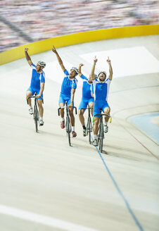 Track cycling team celebrating in velodrome - CAIF03793