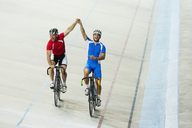 Track cyclists celebrating in velodrome - CAIF03799