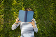 Girl lying on meadow reading a book - LVF06752