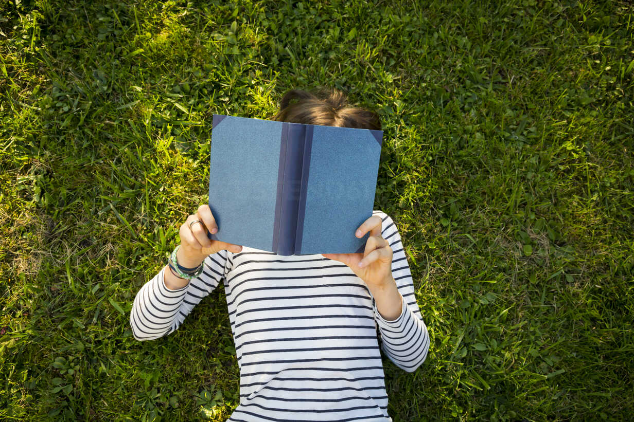 Girl lying on meadow reading a book - LVF06752 - Larissa Veronesi/Westend61