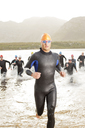 Triathletes in wetsuit running in waves - CAIF03839