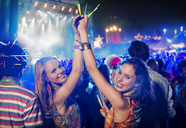 Portrait of cheering women with glow sticks at music festival - CAIF03881