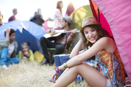 Portrait of woman sitting at front of tent at music festival - CAIF03884
