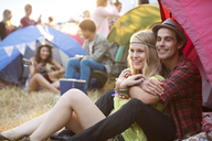 Couple hugging outside tent at music festival - CAIF03893
