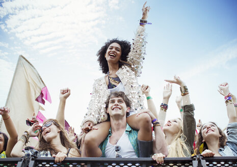 Cheering woman on manÍs shoulders at music festival - CAIF03956
