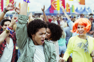 Friends dancing and cheering at music festival - CAIF03959