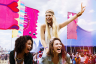 Woman piggybacking enthusiastic friend at music festival - CAIF03968