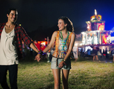 Couple holding hands and leaving music festival - CAIF03980