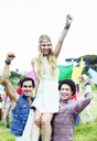 Portrait of men carrying woman at music festival - CAIF03998