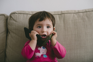 Baby girl playing with two mobilephones at home - GEMF01892