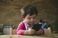 Baby girl using mobile phone at home - GEMF01895