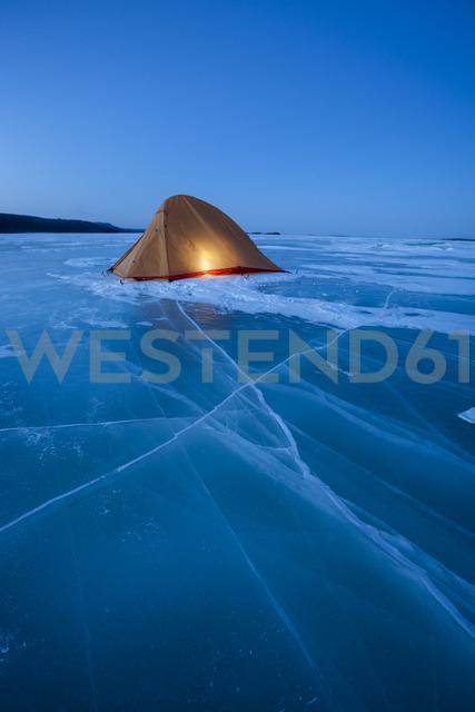 Russia, Amur Oblast, illuminated tent on frozen Zeya River at blue hour - VPIF00376