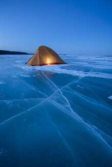 Russia, Amur Oblast, illuminated tent on frozen Zeya River at blue hour - VPIF00376