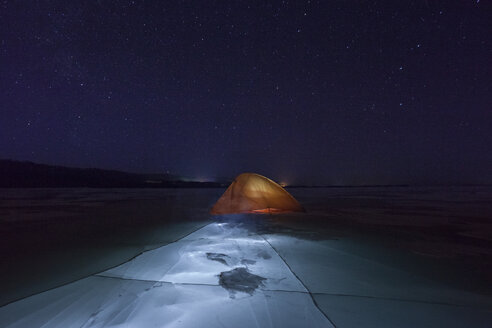 Russia, Amur Oblast, illuminated tent on frozen Zeya River at night under starry sky - VPIF00379