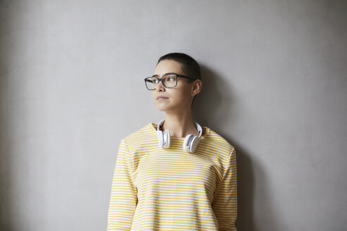 Portrait of short-haired young woman wearing glasses and headphones - FMKF04893