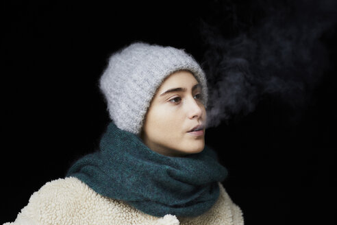 Portrait of  young woman in winter clothes smoking - FMKF04896