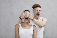 Portrait of screaming young couple wearing vests - FMKF04899