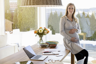 Portrait of smiling pregnant woman working from home - BMOF00005