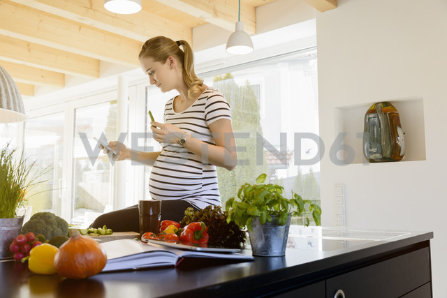 Pregnant woman in kitchen at home using cell phone - BMOF00011 - Buero Monaco/Westend61