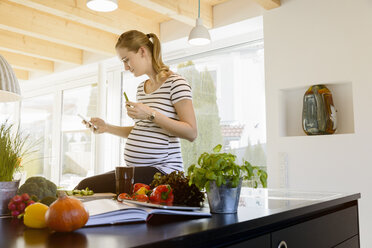 Pregnant woman in kitchen at home using cell phone - BMOF00011