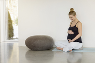 Smiling pregnant woman sitting on a yoga mat - BMOF00014