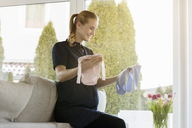 Smiling pregnant woman holding baby clothes at home - BMOF00017