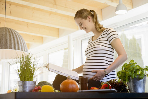 Smiling pregnant woman reading book in kitchen at home - BMOF00026