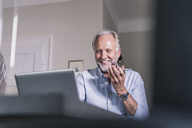 Portrait of smiling mature man using laptop and cell phone at home - UUF12928