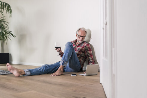 Barefoot man sitting on the floor at home relaxing with laptop and glass of red wine - UUF12952