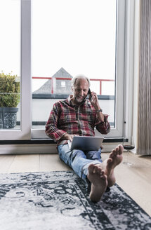 Barefoot man on the phone relaxing on the floor at home with laptop and glass of red wine - UUF12955