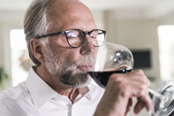 Portrait of mature man drinking glass of red wine - UUF12958