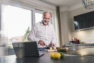Mature man preparing food in the kitchen while looking at laptop - UUF12964