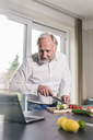 Mature man preparing vegetables in the kitchen while looking at laptop - UUF12967