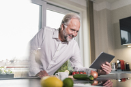 Smiling mature man using tablet in the kitchen - UUF12970