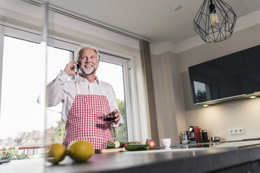 Portrait of relaxed mature man on the phone in the kitchen - UUF12973