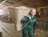 Portrait of smiling female farmer in stable on a farm carrying basket with straw - CVF00253