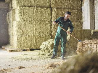 Farmer working with straw on a farm - CVF00256