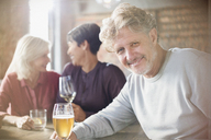 Portrait smiling senior man drinking beer dining with friends at restaurant table - HOXF00010