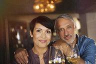 Portrait confident couple drinking white wine in bar - HOXF00013