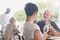 Couple talking and drinking white wine at outdoor restaurant table - HOXF00028